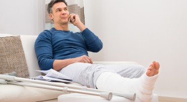 Man With Fractured Leg Sitting On Sofa Talking On Cellphone